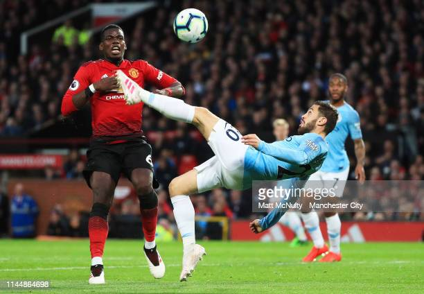 Bernardo Silva of Manchester City shoots while under pressure from Paul Pogba of Manchester United during the Premier League match between Manchester...