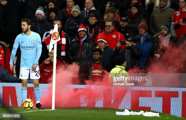 Bernardo Silva of Manchester City stands to take a corner as a flare goes off in the background during the Premier League match between Manchester...