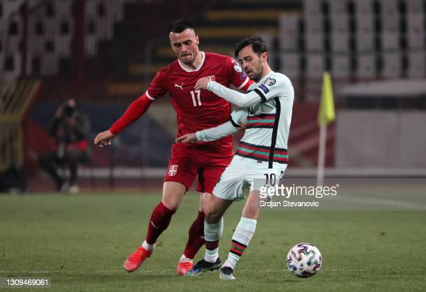 Bernardo Silva of Portugal and Filip Kostić of Serbia battle for the ball during the FIFA World Cup 2022 Qatar qualifying match between Serbia and...