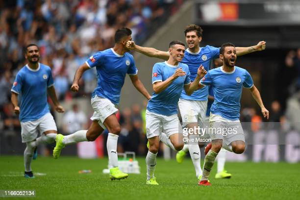 Bernardo Silva, Phil Foden and John Stones of Manchester City celebrate following their team's victory in the penalty shoot out during the FA...