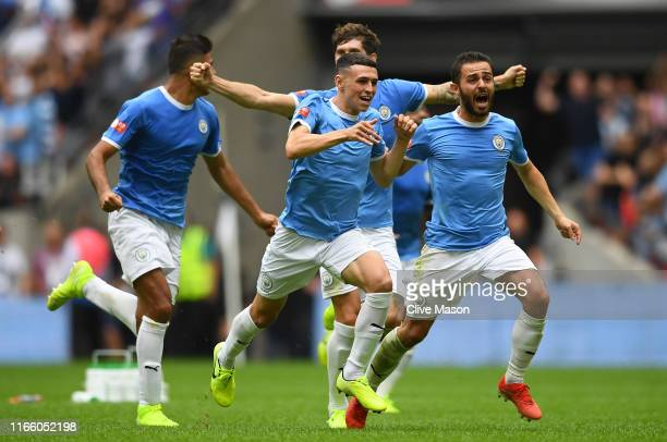 Bernardo Silva Phil Foden and John Stones of Manchester City celebrate following their team's victory in the penalty shoot out during the FA...