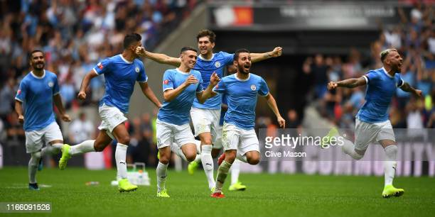 Bernardo Silva Phil Foden and John Stones of Manchester City celebrate following their team's victory in the penalty shoot out during during the FA...