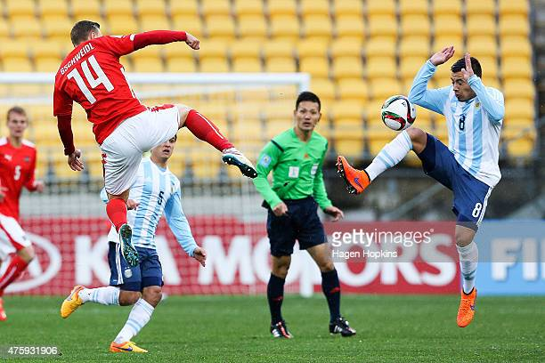 Bernd Gschweidl of Austria and Leonardo Rolon of Argentina compete for the ball while referee Ryuji Sato of Japan looks on during the FIFA U20 World...