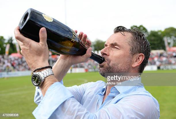 Bernd Hollerbach drinks champaign and celebrates his teams promotion to the third league after winning the Regionalliga Playoffs match between...