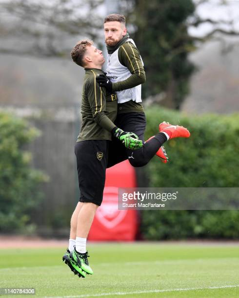 Bernd Leno and Shkodran Mustafi of Arsenal jump up together during a training session at London Colney on April 06 2019 in St Albans England