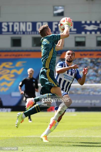 Bernd Leno of Arsenal attempts to collect the ball as he collides with Neal Maupay of Brighton and Hove Albion and later goes down injured during the...