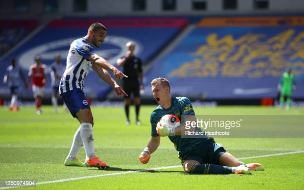 Bernd Leno of Arsenal collects the ball and injuries himself as Neal Maupay of Brighton and Hove Albion reacts during the Premier League match...