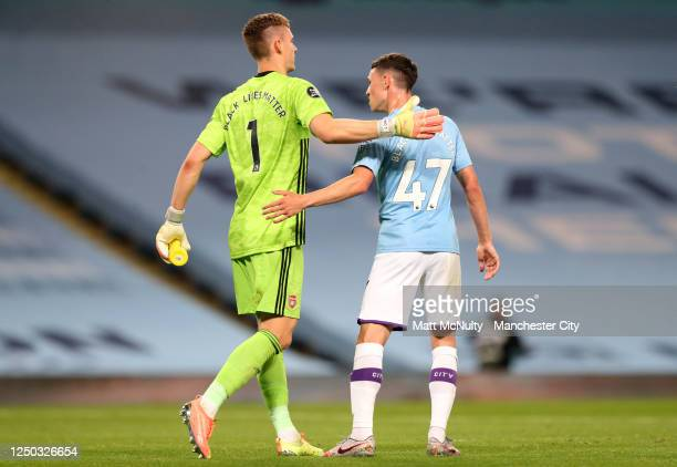 Bernd Leno of Arsenal embraces Phil Foden of Manchester City at fulltime after the Premier League match between Manchester City and Arsenal FC at...