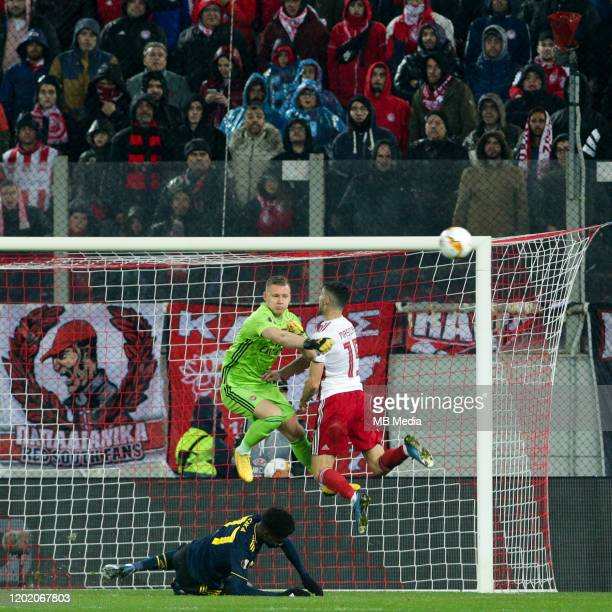 Bernd Leno of Arsenal FC and Giorgos Masouras of Olympiacos FC during the UEFA Europa League round of 32 first leg match between Olympiacos FC and...