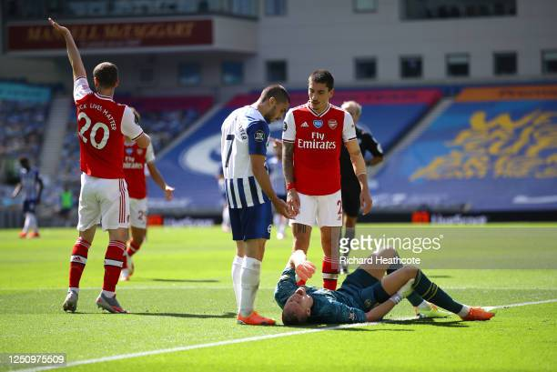 Bernd Leno of Arsenal goes down injured and in pain as Neal Maupay of Brighton and Hove Albion and Hector Bellerin react during the Premier League...