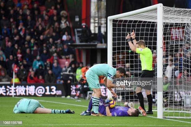 Bernd Leno of Arsenal is checked on by Sokratis of Arsenal after a clash with Callum Wilson of AFC Bournemouth during the Premier League match...