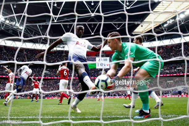 Bernd Leno of Arsenal makes a save as Victor Wanyama of Tottenham Hotspur battles for possession during the Premier League match between Tottenham...