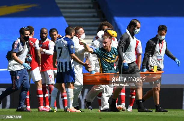 Bernd Leno of Arsenal points towards Neal Maupay of Brighton and Hove Albion as he is stretched off injured during the Premier League match between...