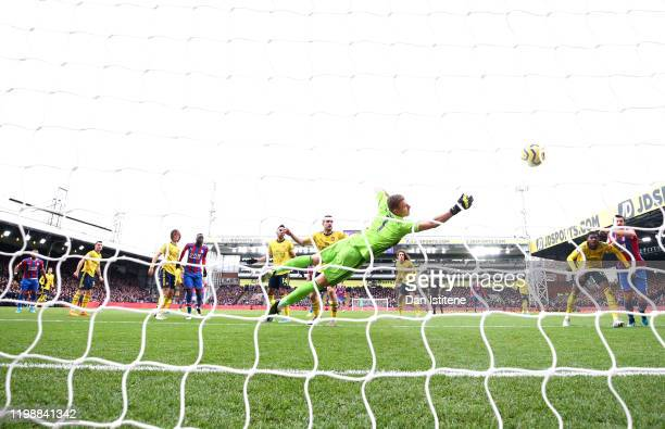 Bernd Leno of Arsenal reaches for the ball as Jordan Ayew of Crystal Palace scores his team's first goal during the Premier League match between...