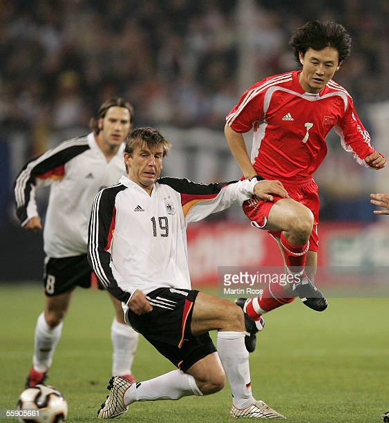 Bernd Schneider of Germany and Jihai Sun of China fight for the ball during the friendly game between Germany and China at the AOL Arena on October...