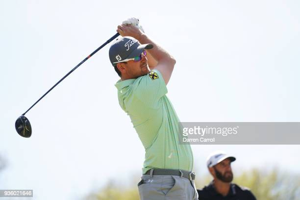 Bernd Wiesberger of Austria plays his shot from the 12th tee as Dustin Johnson of the United States looks on during the first round of the World Golf...
