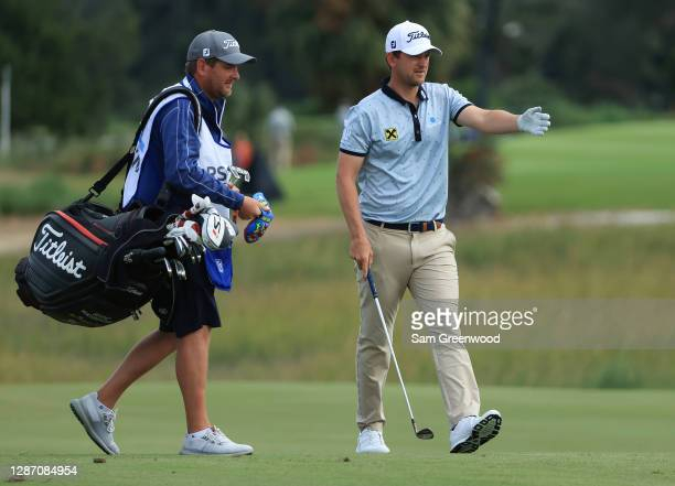 Bernd Wiesberger of Austria talks with his caddie on the 13th green during the final round of The RSM Classic at the Seaside Course at Sea Island...
