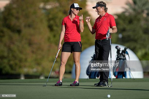 Bernhard and Christina Langer of Germany discuss a putt on the 18th green during the first round of the PNC Father/Son Challenge at The RitzCarlton...