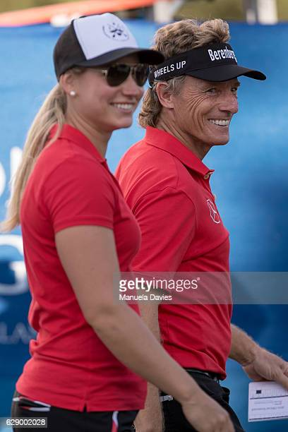Bernhard and Christina Langer of Germany leave the 18th green after the first round of the PNC Father/Son Challenge at The RitzCarlton Golf Club on...