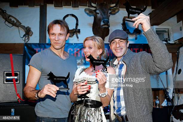 Bernhard Bettermann Eva Habermann and Gedeon Burkhard receive an award at the Dorfstadl Evening Tirol Cross Mountain 2013 on December 07 2013 in...
