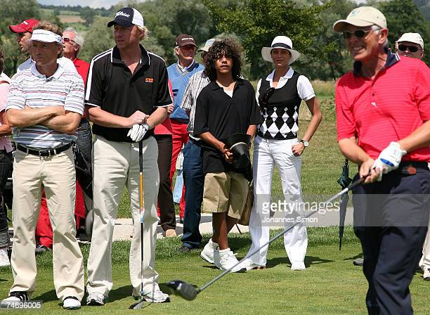 Bernhard Langer and Boris Becker wait on the 18th hole watched by Boris's son Noah and his girlfriend Sharlely Lilly Kerssenberg during the opening...