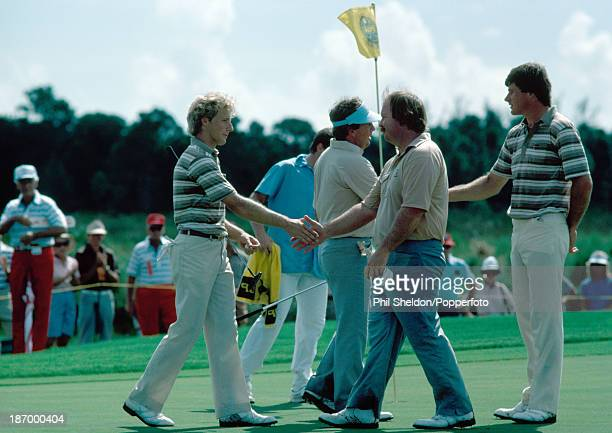 Bernhard Langer and Nick Faldo of the European team shake hands with Lanny Wadkins and Craig Stadler of the United States team after Faldo and Langer...
