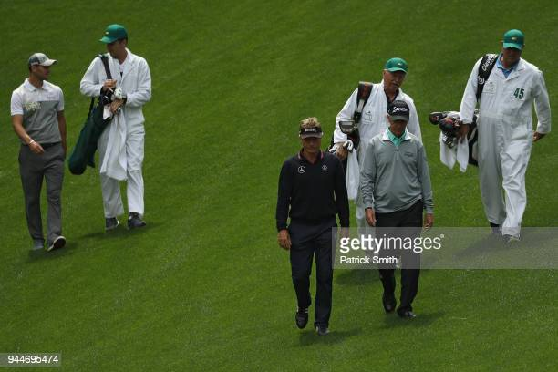 Bernhard Langer of Germany and Oliver Bierhoff walk to the green during the Par 3 Contest prior to the start of the 2018 Masters Tournament at...