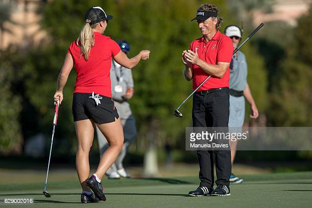 Bernhard Langer of Germany applauds daughter Christina's putt on the 18th green during the first round of the PNC Father/Son Challenge at The...