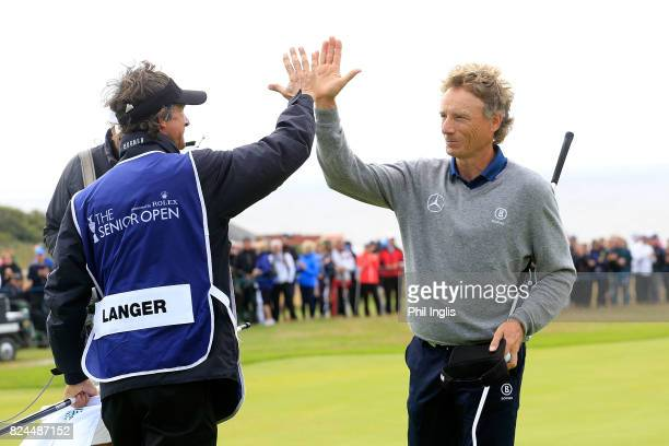 Bernhard Langer of Germany hi fives with his caddie Terry Holt during the final round of the Senior Open Championship at Royal Porthcawl Golf Club on...