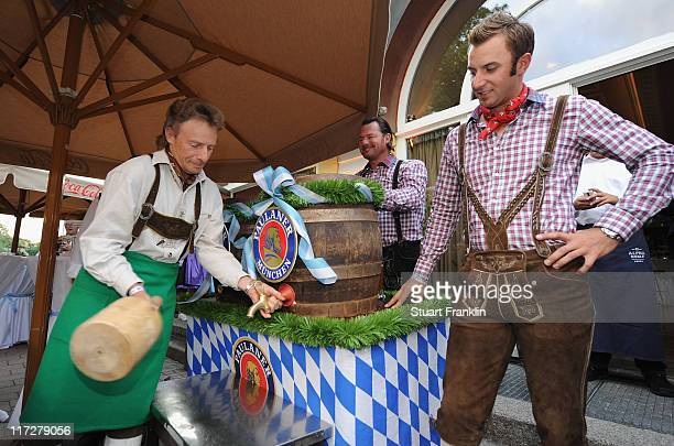 Bernhard Langer of Germany knocks a spout in the beer keg as he is watched by Dustin Johnson of USA as they wear the traditional lederhosen costumes...
