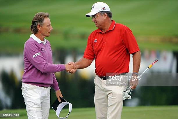 Bernhard Langer of Germany shakes hands with Kenny Perry on the 18th hole after finishing their round during the second round of the 3M Championship...