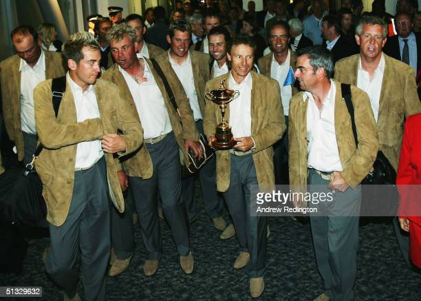Bernhard Langer of Germany the team captain holds the trophy alongside his victorious European Ryder Cup teammates as they arrive at Heathrow airport...