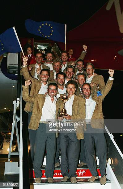 Bernhard Langer of Germany the team captain poses with the trophy and his teammates as the victorious European Ryder Cup team arrive at Heathrow...