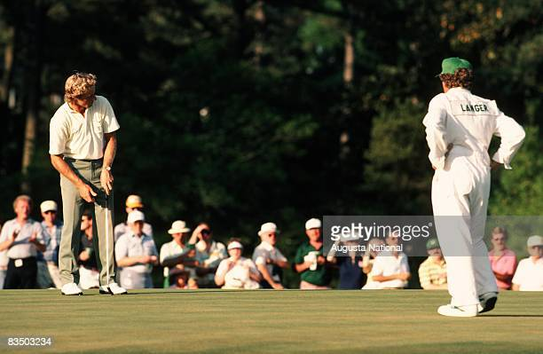 Bernhard Langer watches his putt with his caddie in front of a small gallery during the 1986 Masters Tournament at Augusta National Golf Club in...