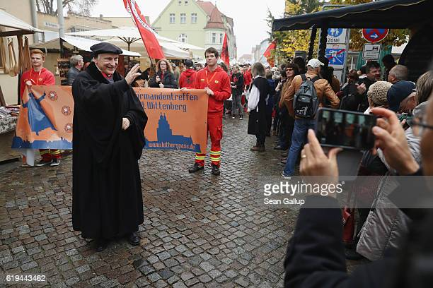 Bernhard Neumann who is the sexton at the Schlosskirche church is dressed as reformist theologian Martin Luther as he greets onlookers near the...