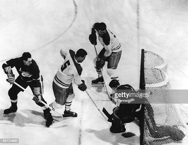 Bernie Boom Boom Geoffrion of the Montreal Canadiens scores past goalie Terry Sawchuk of the Detroit Red Wings as Red Kelly of the Red Wings defends...