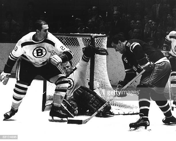 """Bernie """"Boom Boom"""" Geoffrion of the New York Rangers tries to backhand a shot against goalie Gerry Cheevers of the Boston Bruins as his teammate Leo..."""