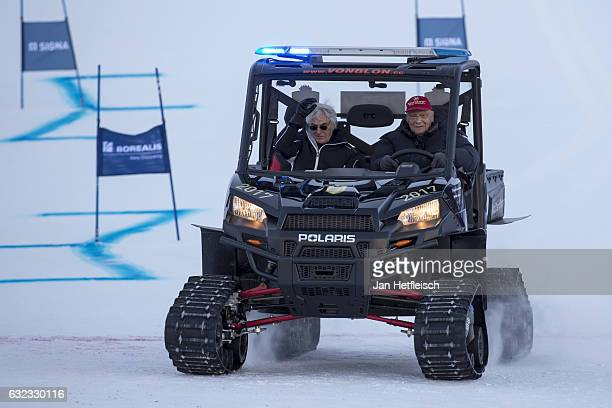 Bernie Ecclestone and former Formula One champion Niki Lauda drive with a snowmobile on a slope in Kitzbuehel before the KitzCharityTrophy on January...