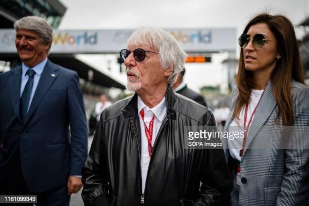 Bernie Ecclestone , Chairman Emeritus of the Formula One Group and his wife Fabiana Flosi walk through the starting grid prior to the Austrian MotoGP...