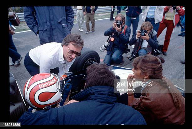 Bernie Ecclestone owner of the Brabham Grand Prix team left talks with driver Nelson Piquet as he sits in his car on the starting grid for the 1983...
