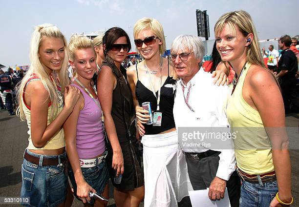 Bernie Ecclestone pose on the starting grid with the girls for the photographers before the Hungarian F1 Grand Prix on July 31, 2005 in Budapest,...