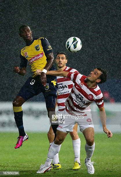 Bernie Ibini of the Mariners is challenged by Mark Bridge of the Wanderers during the round 23 ALeague match between the Central Coast Mariners and...