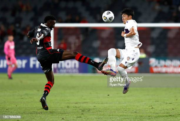 Bernie Ibini of the Wanderers competes for the ball against Kosuke Ota of the Glory during the A-League match between the Western Sydney Wanderers...