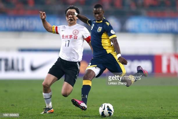 Bernie Ibinie of the Mariners challenges Sun Jihai of Guizhou Renhe during the AFC Champions League match between Guizhou Renhe and Central Coast...