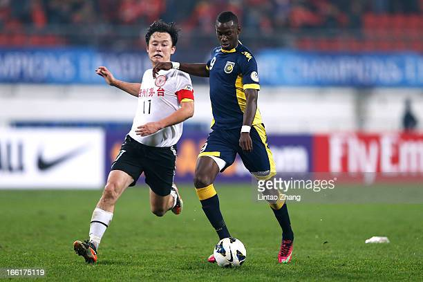 Bernie Ibini-Isei of the Mariners challenges Sun Jihai of Guizhou Renhe during the AFC Champions League match between Guizhou Renhe and Central Coast...