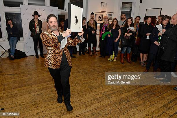 Bernie Katz displays artwork up for auction at the Murray Parish Trust inaugural art auction at The Gallery Soho on February 6 2014 in London England