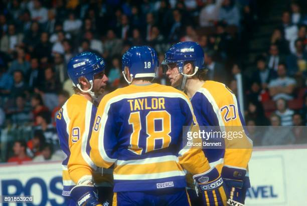 Bernie Nicholls Dave Taylor and Luc Robitaille of the Los Angeles Kings talk on the ice during an NHL game against the Philadelphia Flyers circa 1987...