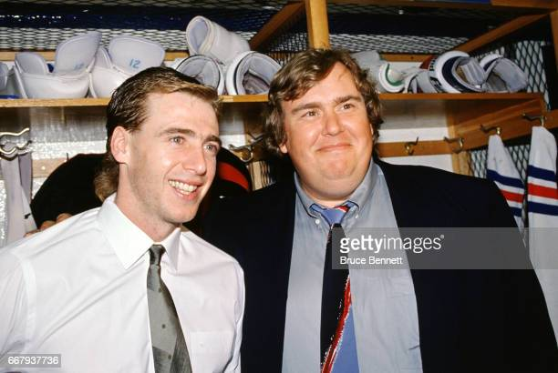 Bernie Nicholls of the New York Rangers poses for a portrait in the locker room with actor and comedian John Candy circa March 1990 at Madison Square...