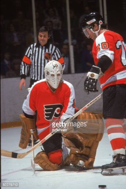 Bernie Parent goalkeeper for the Philadelphia Flyers on the ice with teammate Jimmy Watson and an unidentified referee during a road game against the...
