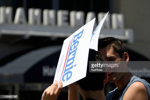 Bernie Sanders campaign posters are used by supporters to protect from the impact of the blazing son during a midday rally protesting the imminent...
